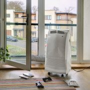 Gree 3.5kW portable air conditioner in a lounge with hose going out the balcony