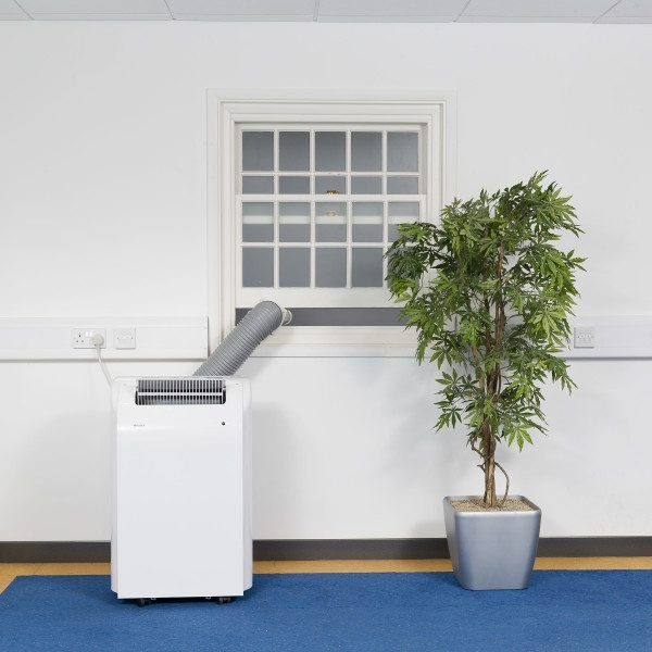 White Airconco 4.1kW portable air conditioner in an office with hose going out the window.