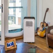 Airconco Mini portable air conditioner in a Home with hose going out balcony door.
